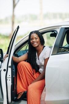 Mujer sonriente sentada en coche nuevo