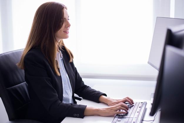 Mujer sonriente sentada escribiendo en un ordenador