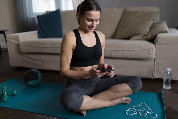 Mujer sonriente sentada en la estera de yoga y mirando el teléfono