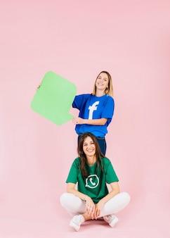 Mujer sonriente sentada frente a su amiga con bocadillo de diálogo verde
