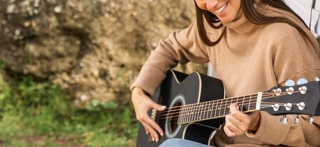 Mujer sonriente sentada en el maletero del coche durante un viaje por carretera y tocando la guitarra