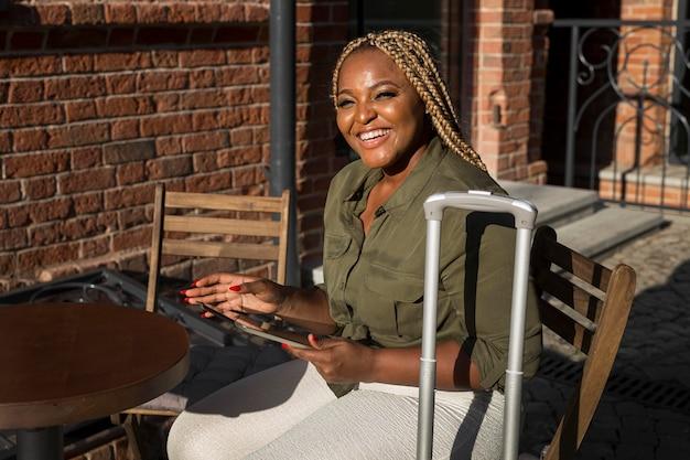 Mujer sonriente sentada en una mesa mientras revisa su tableta
