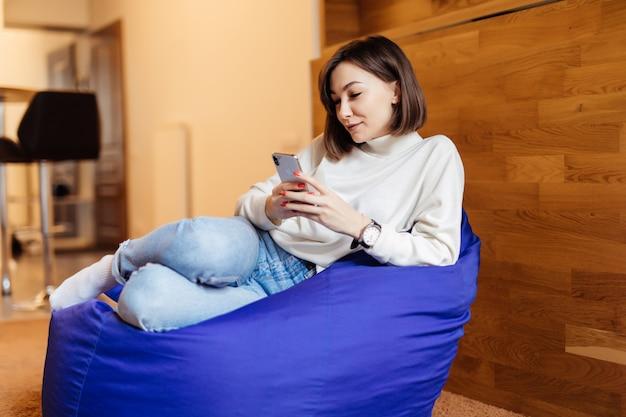 La mujer sonriente está sentada en una silla de bolso violeta brillante usando su teléfono para enviar mensajes de texto con sus amigos