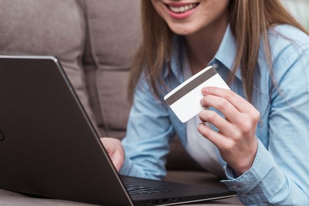 Mujer sonriente sentada en el sofá y sosteniendo el primer plano de la tarjeta de crédito