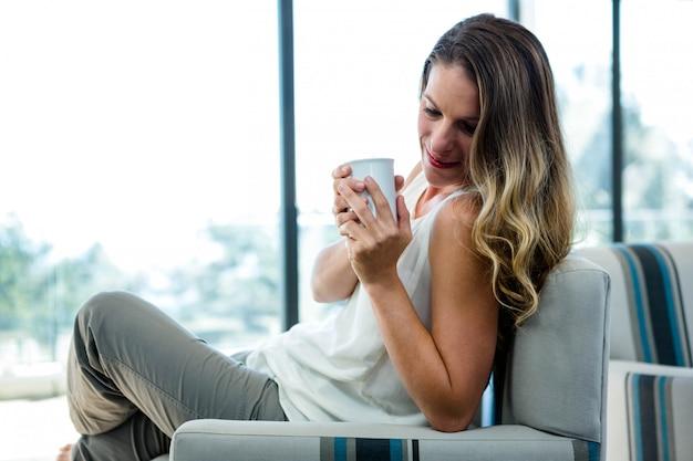 Mujer sonriente sentada en un sofá, tomando una taza de café