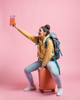 Mujer sonriente sentada en su equipaje