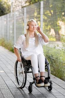 Mujer sonriente en silla de ruedas con auriculares al aire libre