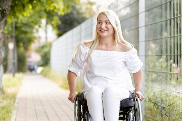 Mujer sonriente en silla de ruedas en la ciudad