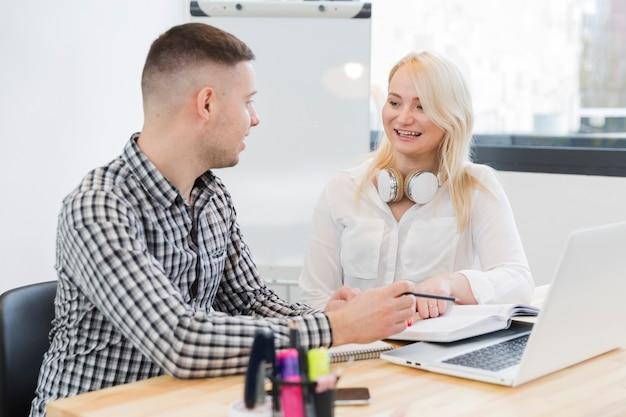 Mujer sonriente en silla de ruedas conversando con un colega
