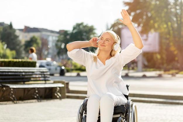 Mujer sonriente en silla de ruedas disfrutando de música en auriculares