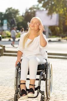 Mujer sonriente en silla de ruedas escuchando música con auriculares fuera