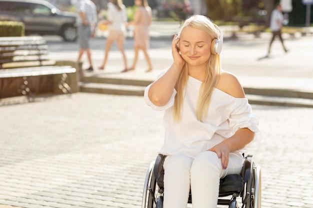 Mujer sonriente en silla de ruedas escuchando música con auriculares