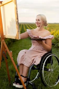 Mujer sonriente en silla de ruedas pintando al aire libre