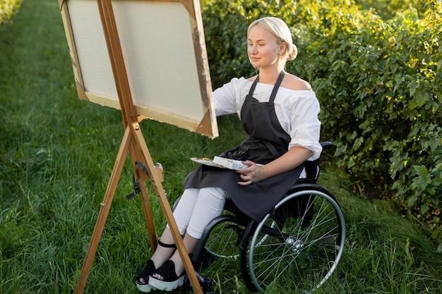 Mujer sonriente en silla de ruedas pintando en la naturaleza