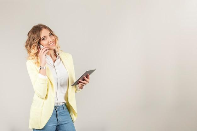 Mujer sonriente con smartphone y tablet