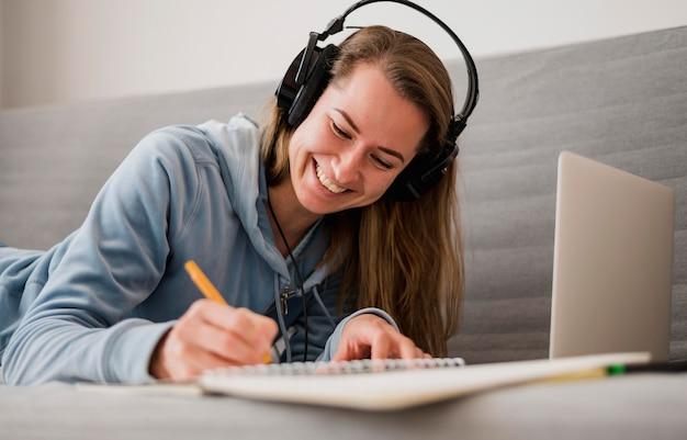Mujer sonriente en el sofá asistiendo a una clase en línea