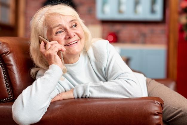 Mujer sonriente en el sofá hablando por teléfono