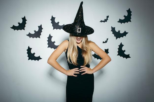 Mujer sonriente con sombrero de bruja