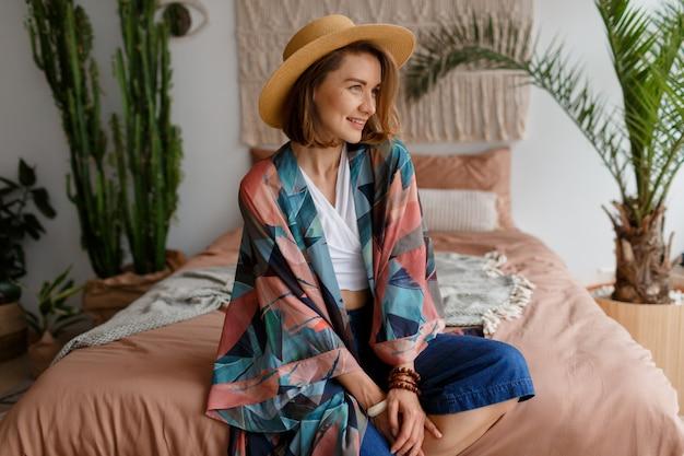 Mujer sonriente en sombrero de paja que se enfría en casa en el acogedor interior de boho