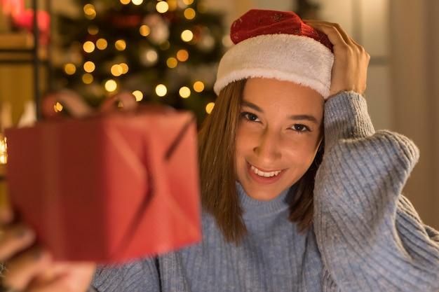 Mujer sonriente con sombrero de santa con regalo de navidad
