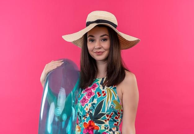 Mujer sonriente con sombrero sosteniendo anillo de natación en pared rosa aislada