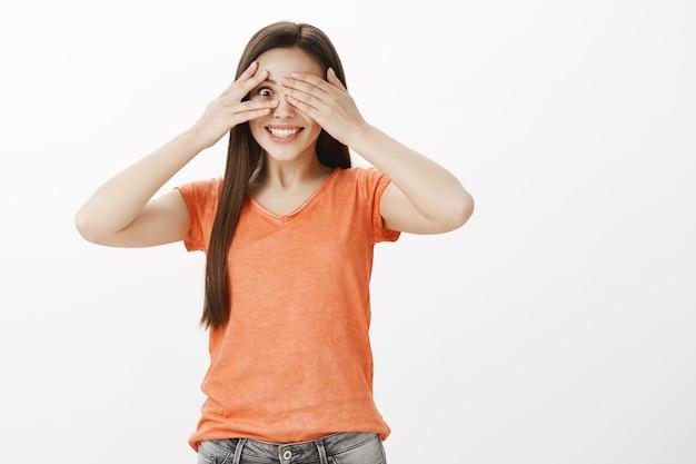 Mujer sonriente soñadora y esperanzada cerrar los ojos, mirando a través de los dedos impresionado