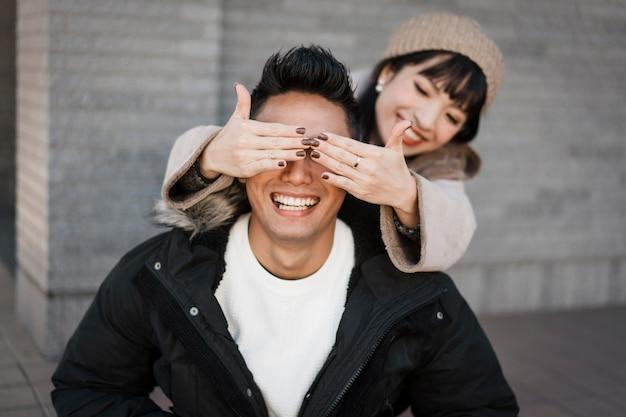 Mujer sonriente sorprende a su novio al aire libre
