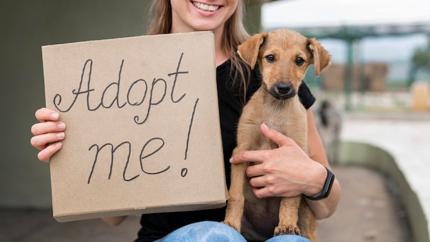 Mujer sonriente sosteniendo adoptarme signo y perro de rescate