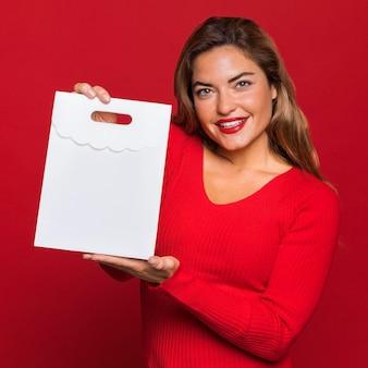 Mujer sonriente sosteniendo una bolsa de papel