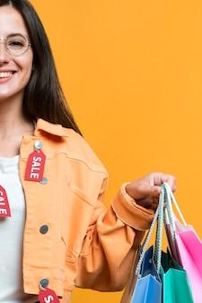 Mujer sonriente sosteniendo bolsas de la compra con chaqueta cubierta de etiquetas
