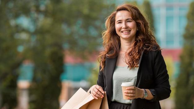Mujer sonriente sosteniendo bolsas de la compra y una taza de café