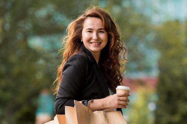 Mujer sonriente sosteniendo bolsas de la compra.