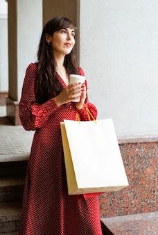 Mujer sonriente sosteniendo bolsas de compras y café