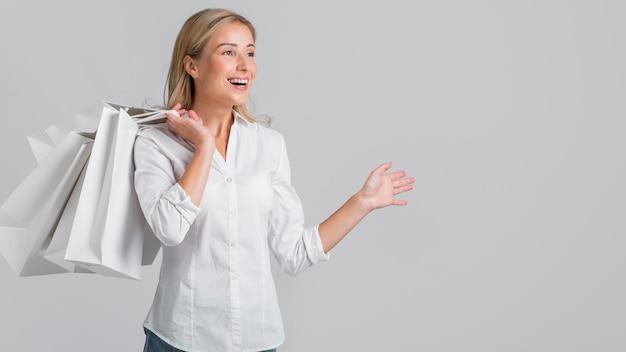 Mujer sonriente sosteniendo bolsas de compras y feliz por la juerga de compras que hizo