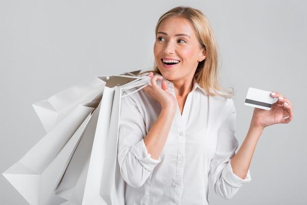 Mujer sonriente sosteniendo bolsas de compras y tarjeta de crédito