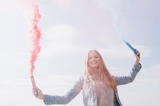 Mujer sonriente sosteniendo bombas de humo de colores