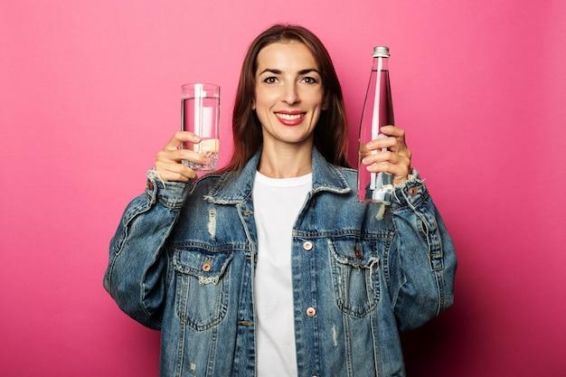 Mujer sonriente sosteniendo una botella de agua y un vaso de agua