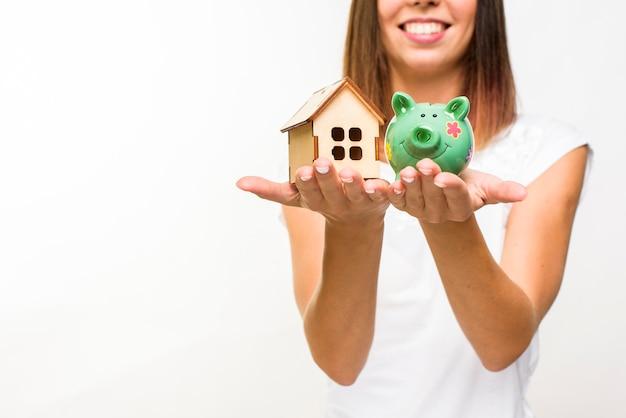 Mujer sonriente sosteniendo una cabaña de madera y un piggy back