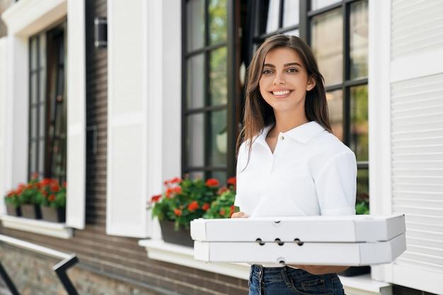 Mujer sonriente sosteniendo cajas de pizza