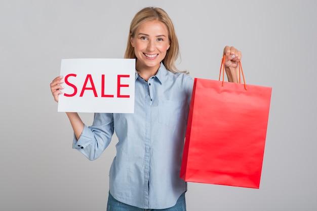 Mujer sonriente sosteniendo cartel de venta y bolsa de compras