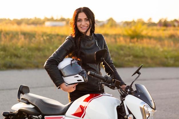 Mujer sonriente sosteniendo casco y posando en su motocicleta