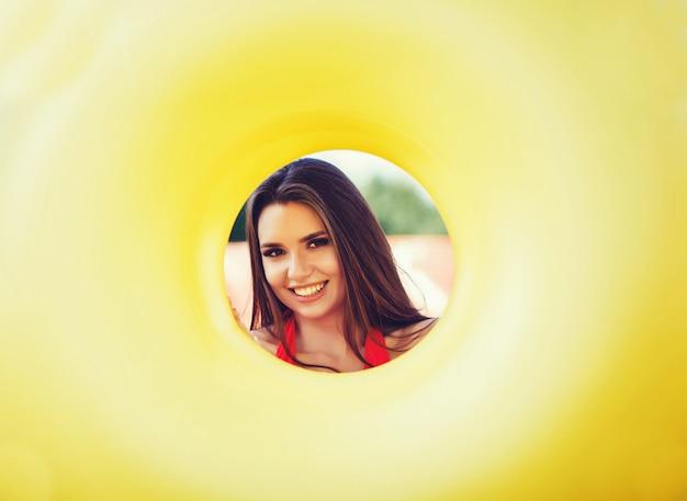 Mujer sonriente sosteniendo círculo inflable