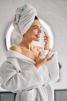 Mujer sonriente sosteniendo una crema para el cuidado de la piel