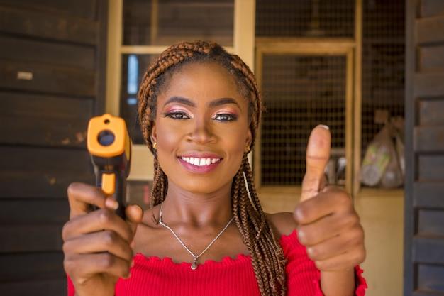 Mujer sonriente sosteniendo un escáner de pistola térmica con los pulgares hacia arriba