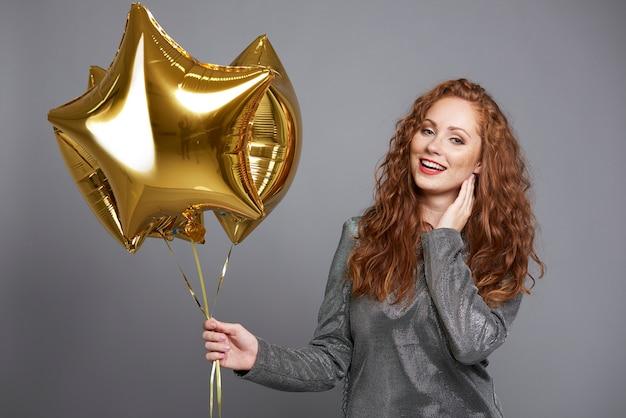 Mujer sonriente sosteniendo globos en forma de estrella