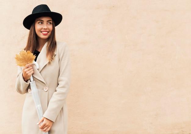 Mujer sonriente sosteniendo una hoja otoñal con espacio de copia