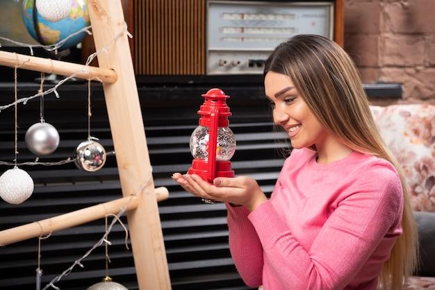 Una mujer sonriente sosteniendo una lámpara roja de navidad. foto de alta calidad