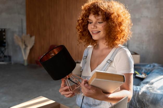 Mujer sonriente sosteniendo libro y lámpara para decorar casa nueva