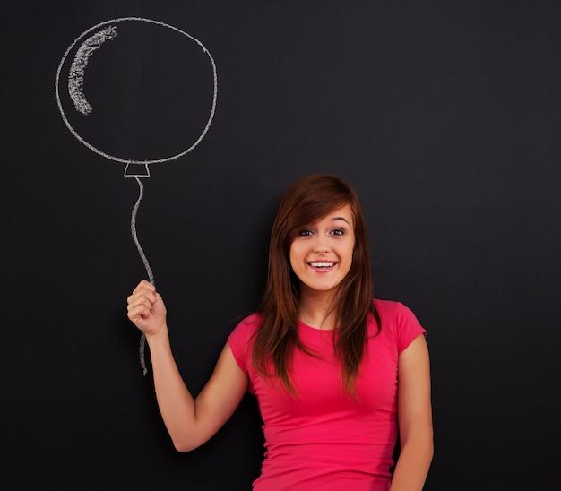Mujer sonriente sosteniendo en la mano globo