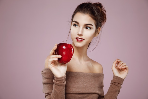 Mujer sonriente sosteniendo manzana roja en rosa
